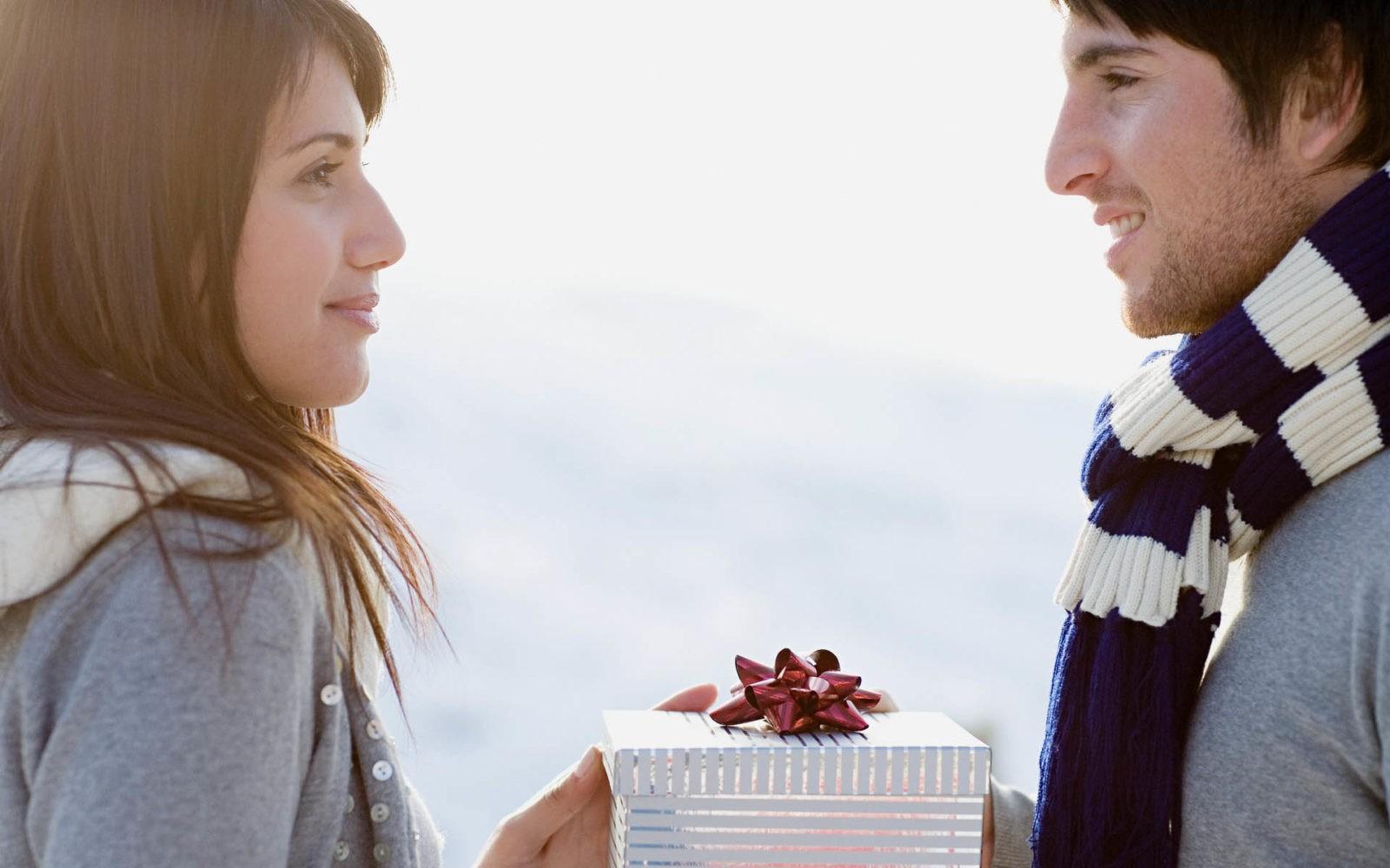 девушка дарит подарок мужчине